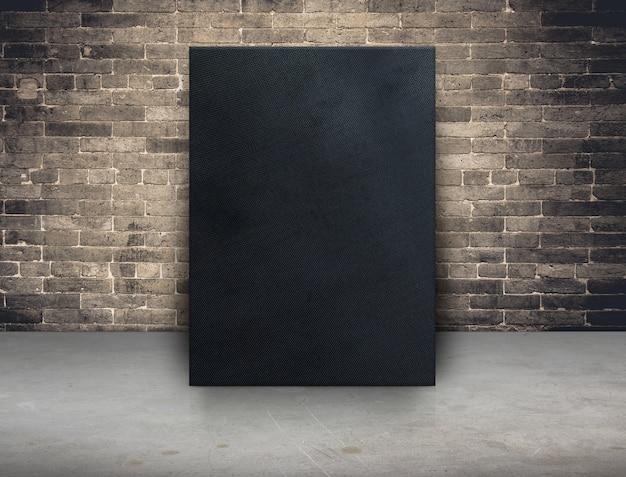 Leerer schwarzer gewebesegeltuchrahmen an der schmutzbacksteinmauer und am konkreten bodenhintergrund