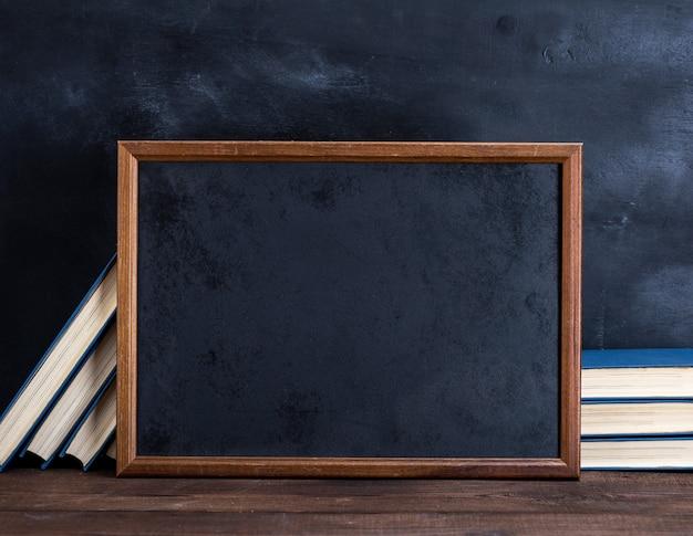 Leerer schwarzer kreidezeichnungsrahmen und stapel bücher