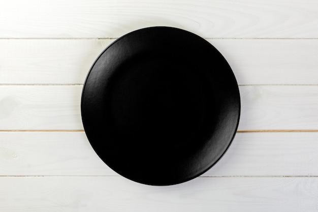 Leerer schwarzer mattteller für abendessen