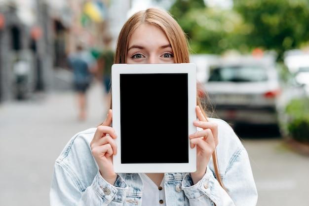 Leerer schwarzer modell ipad bildschirm in den weiblichen händen. mädchen guckt hinter einem bildschirm