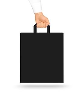 Leerer schwarzer papiertütespott, der in der hand hochhält.