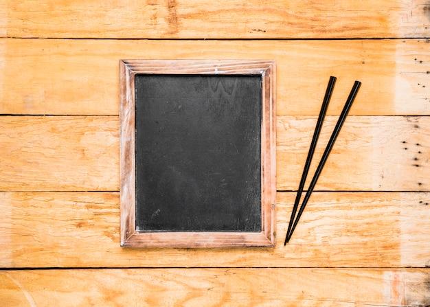 Leerer schwarzer schiefer mit essstäbchen auf hölzerner planke