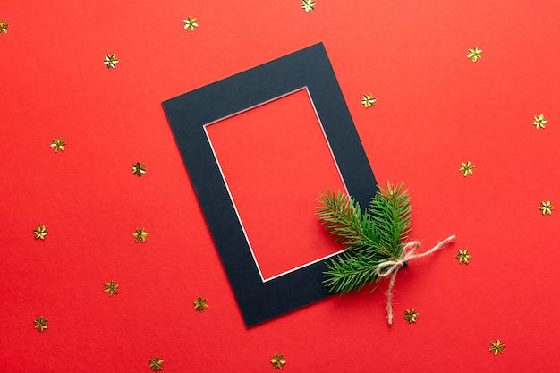 Leerer schwarzer weihnachtspapierrahmen für bild oder foto auf rot