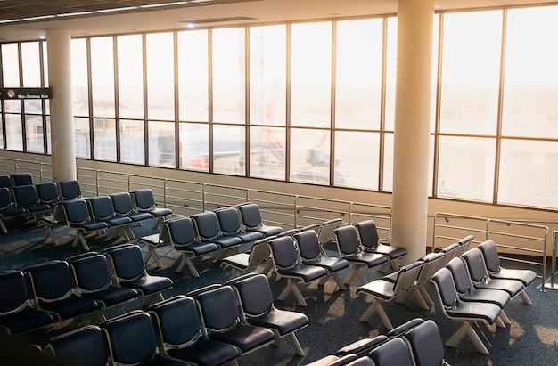 Leerer sitz am tor im flughafen mit sonnenaufgang