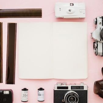 Leerer skizzenbuch inmitten von kameras und film