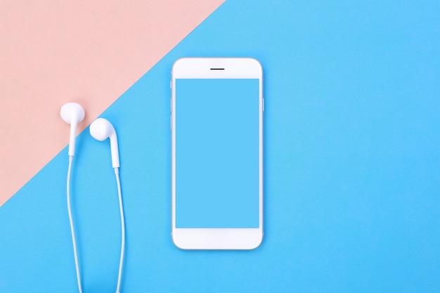 Leerer smartphone und kopfhörer der draufsicht auf blauer und rosa pastelloberfläche