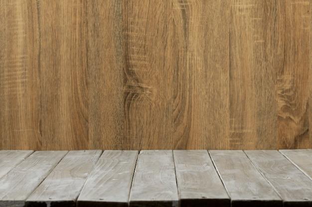 Leerer spitzenholztisch- und holzwandhintergrund