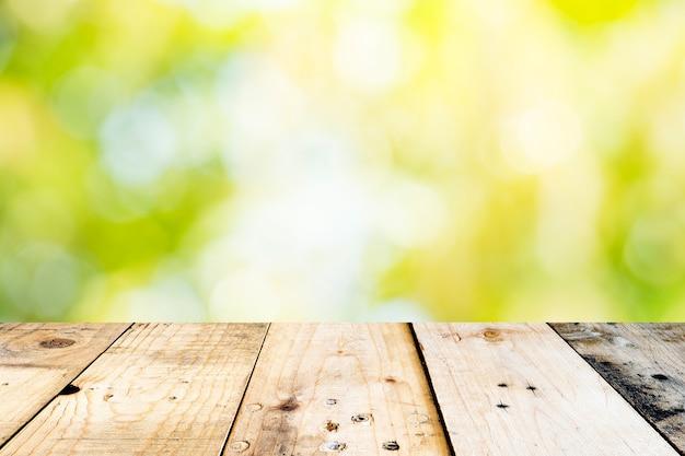 Leerer spitzenholztisch und sonnige zusammenfassung verwischten bokeh hintergrund