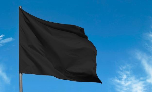Leerer stoff schwarze flagge gegen blauen himmel