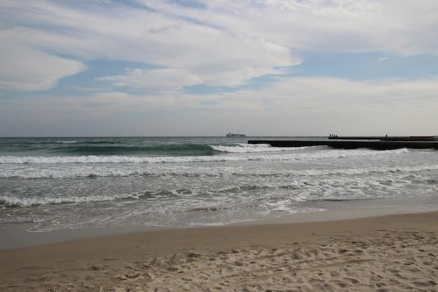 Leerer strand des schwarzen meeres bei bewölktem herbstwetter. landschaft mit stürmischen meereswellen brechen am bewölkten tag um den leeren wilden strand gegen den bewölkten himmel.
