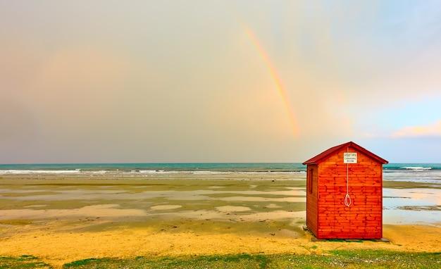 Leerer strand in der nebensaison mit umkleidekabine und regenbogen am himmel, zypern