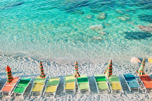 Leerer strand mit geschlossenen regenschirmen auf italienischer küste