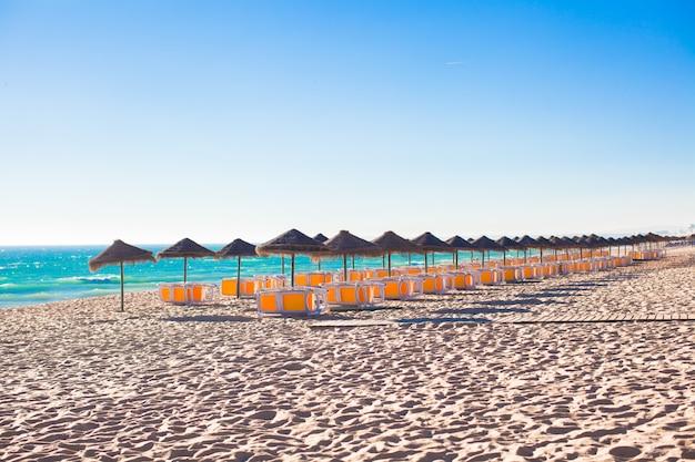Leerer strand mit geschlossenen regenschirmen auf portugiesischer küste