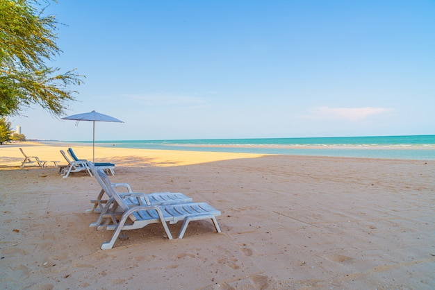 Leerer strandkorb auf sand mit ozeanmeer