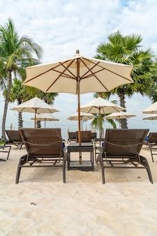 Leerer strandkorb mit palme am strand mit meereshintergrund