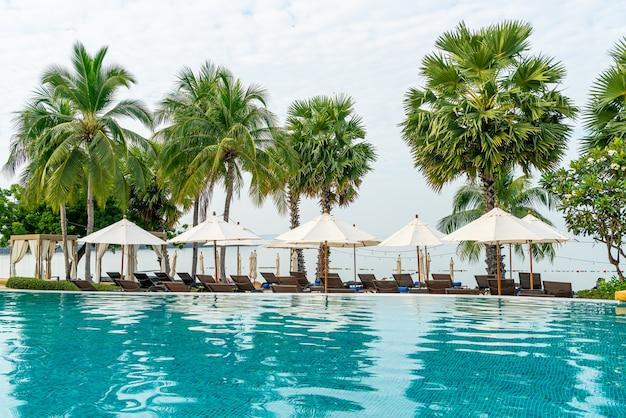 Leerer strandkorb mit sonnenschirm um den pool herum