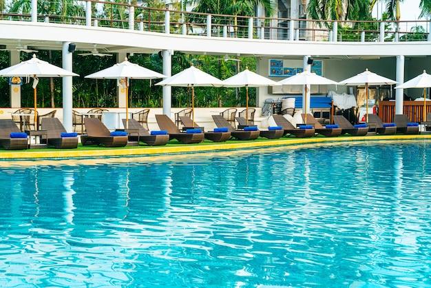 Leerer strandkorb mit sonnenschirm um den pool