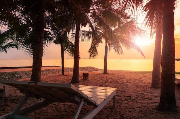 Leerer strandstuhl auf dem schönen tropischen strand und meer zur sonnenuntergangzeit