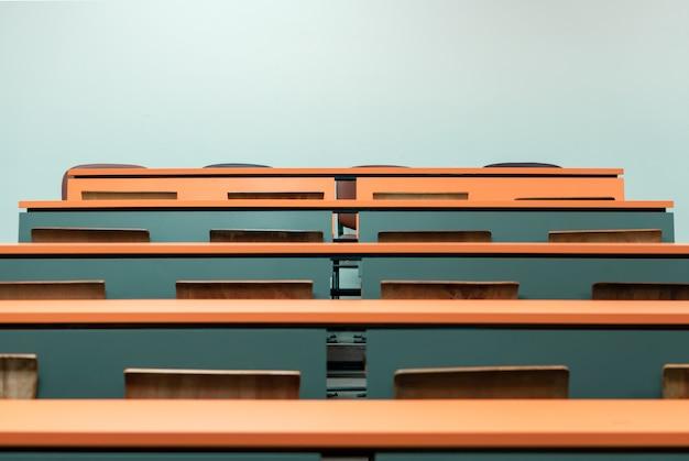 Leerer studentenschreibtisch mit holzstuhl im vorlesungsklassenzimmer des colleges