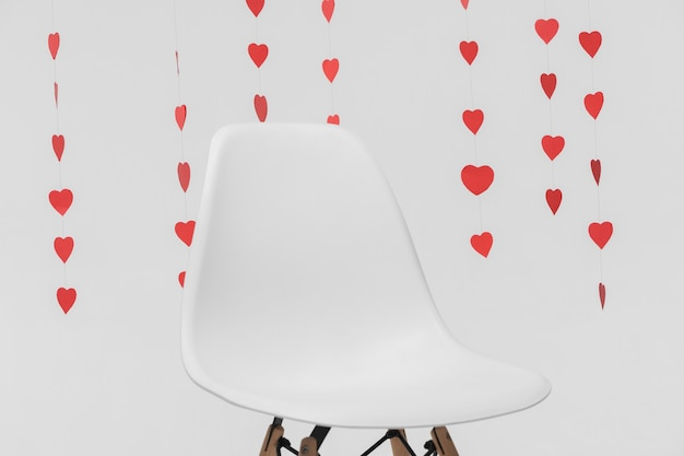 Leerer stuhl der nahaufnahme umgeben durch hängende herzzahlen