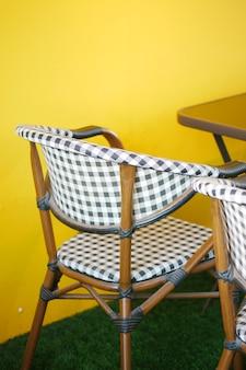 Leerer stuhl im café vor gelbem hintergrund