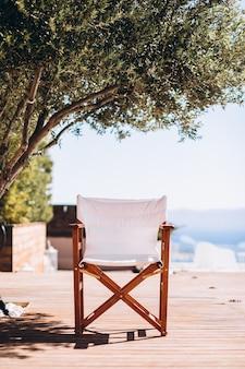 Leerer stuhl unter der palme am strand