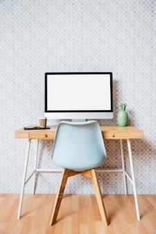 Leerer stuhl vor computer mit leerem weißem schirm