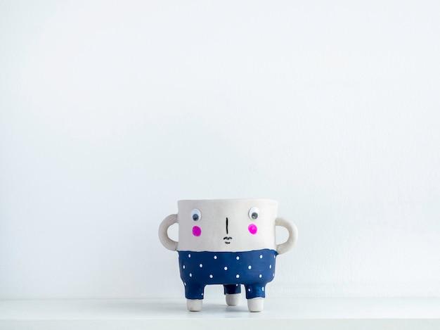 Leerer süßer gesichtskeramik-blumentopf mit auf weißem holzregal isoliert auf weißer wand mit kopierraum. kleine moderne diy-zementpflanzer trendige dekoration.