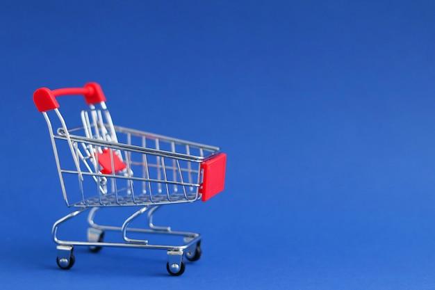 Leerer supermarktwagen, blaue homogene oberfläche, textraum