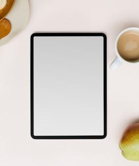Leerer tablet-bildschirm flach neben kaffeetasse