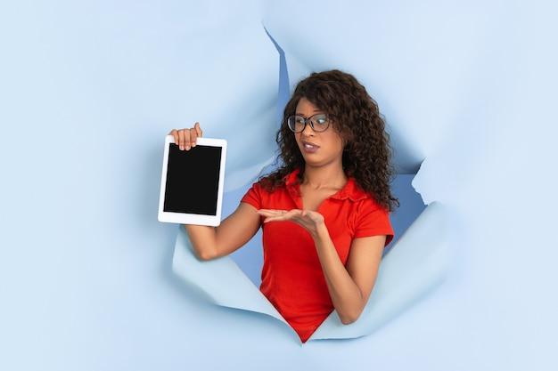 Leerer tablet-bildschirm. fröhliche afroamerikanerin in zerrissenem blauem papierhintergrund, emotional, ausdrucksstark. aufbruch, durchbruch. konzept der menschlichen emotionen, gesichtsausdruck, verkauf, anzeige.