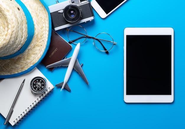 Leerer tablettenschirm für spott oben auf blauem hintergrund mit sommerreisezubehör