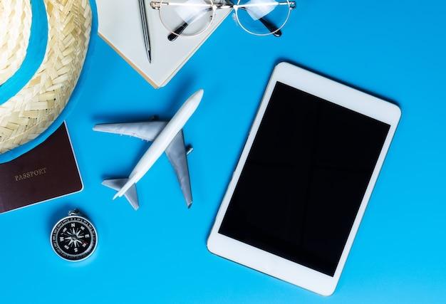 Leerer tablettenspott oben mit reisezubehör auf blauem hintergrund