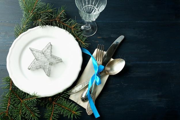 Leerer teller, besteck, serviette und glas auf rustikaler holzoberfläche. weihnachtstischdekorationskonzept