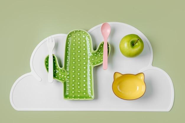 Leerer teller in form eines kaktus und einer katze auf dem tisch. süße kinderteller