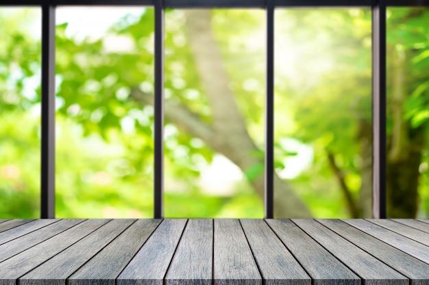 Leerer tisch der perspektivischen holzplatte oben über unscharfem natürlichem hintergrund.