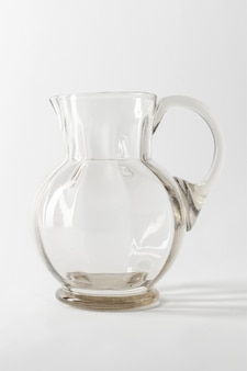 Leerer transparenter glaskrug auf grau