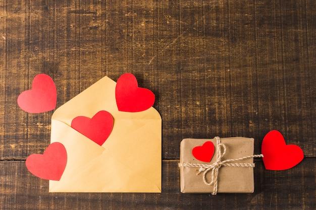 Leerer umschlag; herzen und geschenkbox mit braunem papier umwickelt angeordnet über strukturierte oberfläche