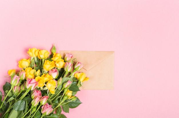 Leerer umschlag mit platz für text für frühlingsgrußkarte. rosen auf rosa hintergrund. flache lage, draufsicht