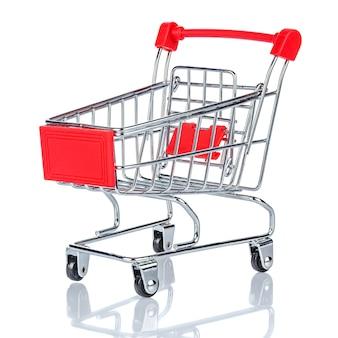 Leerer verchromter spielzeugmarkt-einkaufswagen mit rotem griff und kunststoffplatte auf der vorderseite. weißer hintergrund mit reflexion auf der glänzenden glasoberfläche