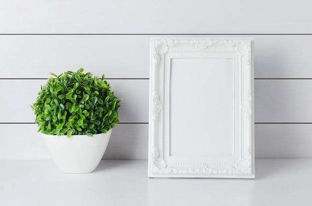 Leerer vintage fotorahmen mit grüner hauptpflanze