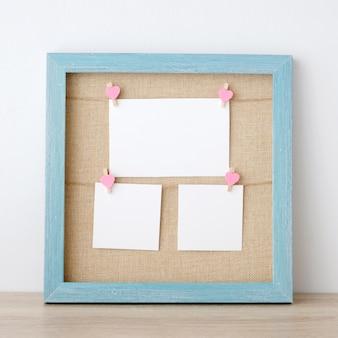 Leerer weißbuchnotizblock, der am blauen hölzernen rahmenhintergrund der weinlese hängt