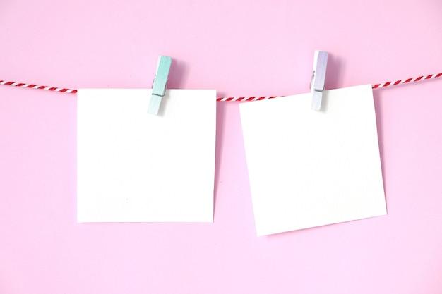 Leerer weißbuchnotizblock, der am rosa hintergrund hängt