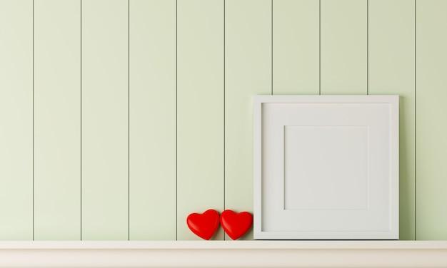 Leerer weißer bilderrahmen auf pastellgrüner holzwand mit zwei roten herzen.