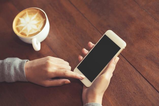 Leerer weißer bildschirm des handy-modellbildes. hand der frau, die sms unter verwendung des handys auf schreibtisch am kaffeehaus hält.