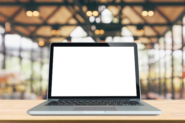 Leerer weißer bildschirm laptop-computer auf holztischplatte mit abstraktem bokeh-licht des caférestaurants defokussierten unscharfen hintergrund