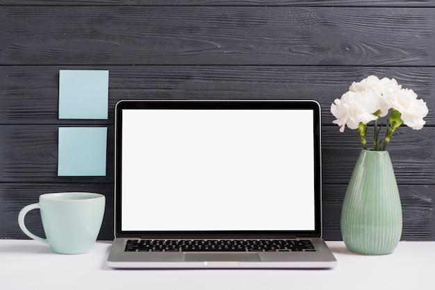 Leerer weißer bildschirmlaptop; blumenvase; tasse auf weißem schreibtisch gegen schwarze holzwand