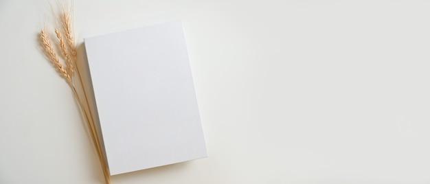 Leerer weißer bucheinband mit trockenem gras und einem leeren raum auf weißem hintergrund