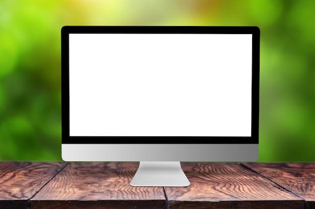 Leerer weißer computermonitor auf einem holztisch gegen verschwommenes grünes natürliches mit bokeh, kopienraum. arbeiten außerhalb des bürokonzepts.