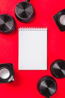 Leerer weißer gewundener notizblock mit kopfhörer und sprecher auf rotem hintergrund